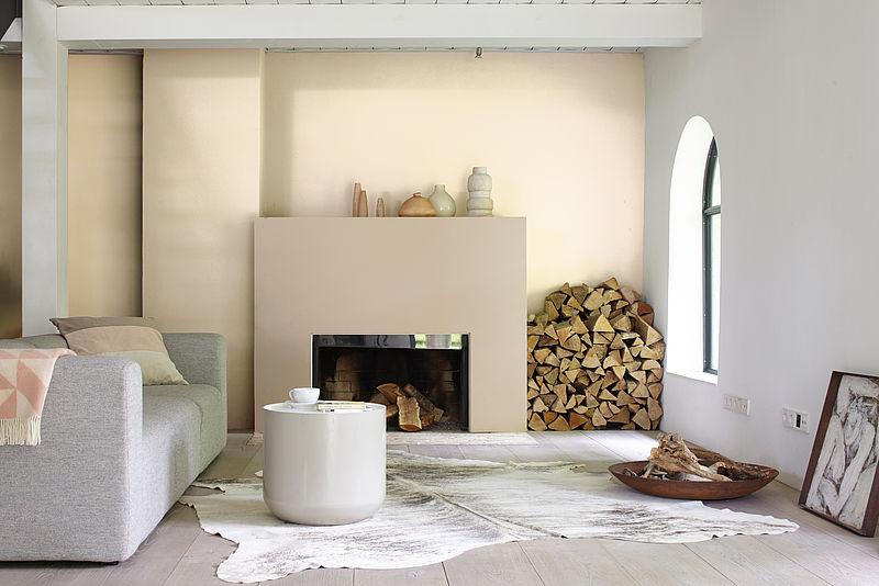 Modernes, elegantes Wohnzimmer in beigen Tönen mit Kamin und grauem Sofa mit Alpina Wandfarbe Zartes Puder.