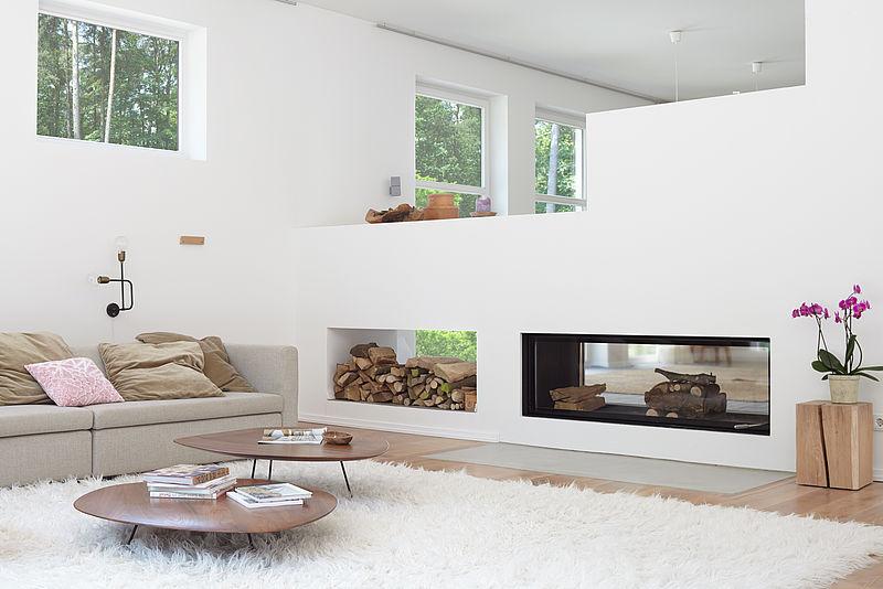 Modernes, weißes Loft mit Kamin, Fellteppich und beigen Sofa in Alpina Weiß.