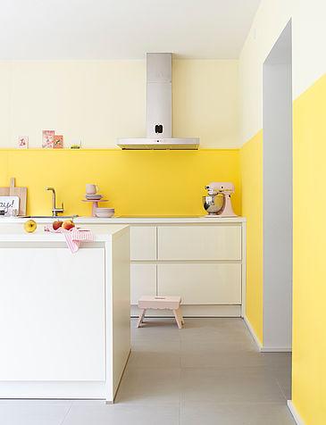 Helle, moderne, weiße Küche mit heller gelber Wand.